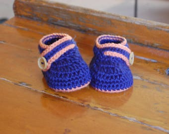 Crochet blue baby booties with orange trim