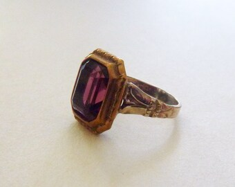 1920s Uncas Egyptian Revival rolled gold plate and brass ring with rectangular purple glass stone size 5