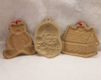 Set of three holiday ceramic cookie presses. Wilton Santa, Brown bag gingerbread house, and Brown bag bear.