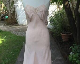 1930's 100 percent pale pink silk slip dress with beautiful antique lace detail around the décolleté. Size medium.