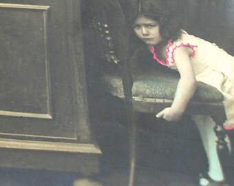 1910s European postcard, girl moving chair. RPPC, real photo postcard, paper ephemera.