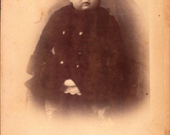 antique cabinet photograph of toddler with a coat and dark hair with bangs