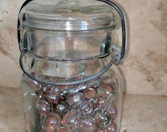 Antique ball jar with glass lid filled with vintage marbles