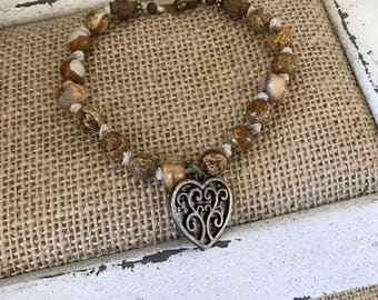 """Brown and Tan on knotted hemp.  Has unique wood crosses and bronze scroll heart charm.  8 1/2"""""""