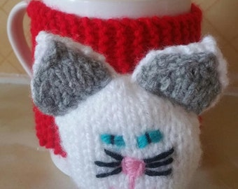Knitted red mug warmer with cat accesory
