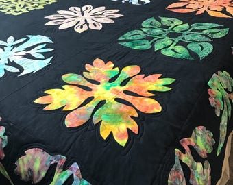 Batik and hand dyed Hawaian Applique sampler on black Kona cotton quilt. This is needle turned appliqué (by hand).