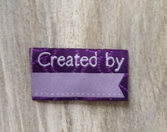 "Fabric label to sew ""Created by"" Purple 45 x 25 mm"