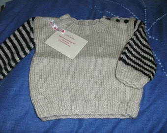 A hand knitted jumper with stripe sleeves