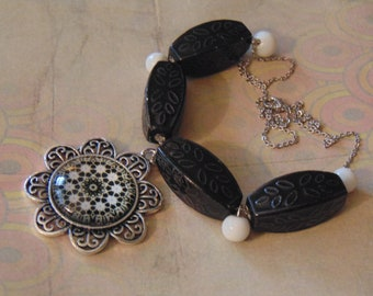Ornate Glass Tarnished Silver Flower Pendant Oblong Black Leaf Pattern Ceramic Bead Round White Ceramic Bead Silver Toned Necklace