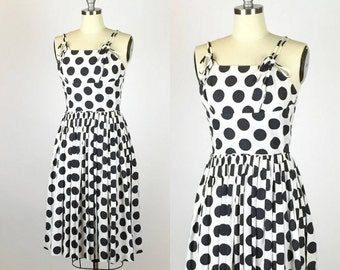 1950s. black and white polka dot day dress. full skirt and adjustable straps. extra small