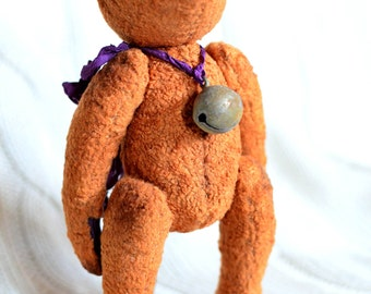 Teddy bear toy of rusty plush with bells and silk ribbon