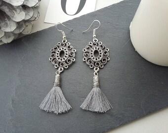 Pattern of filigree and gray tassel earrings