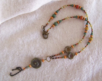 bohemian necklace with a spiral as a symbol in beautiful green and orange colors.