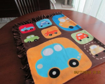 Small child's comfy and warm Fleece Blanket, in bright colors with tassels.