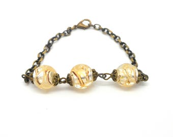 Bracelet bronze beads lined with beige piping