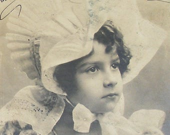 1900s French postcard, Girl in a bonnet, RPPC paper ephemera. Real photo postcard.