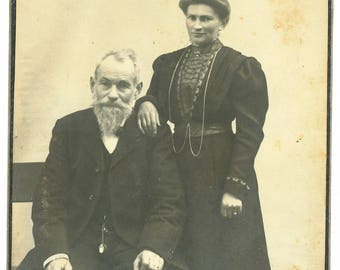 Cabinet card of a couple, the man holds a cigar