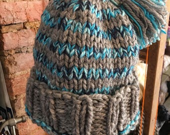 Chapeau d'hiver rayé dans les rayures de votre choix de couleur, tricotés à la main. Pompon en détail. Adulte