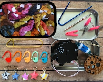 Hand dyed yarn pile: knitting supplies for airplane travel - tiny scissors, crochet hook, origami stitch markers