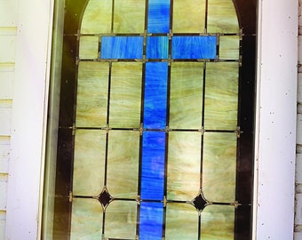 Photo of blue cross stained glass window in an old church in North Carolina