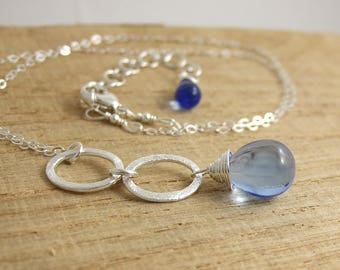 Necklace with a Pendant of Two Brushed Sterling Silver Loops and a Sapphire Blue Glass Teardrop Wire Wrapped with Sterling Silver CDN-716