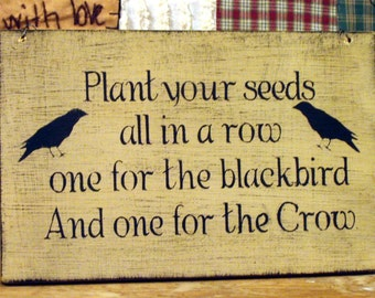 Plant your seeds all in a row one for the blackbird and one for the crow wood sign