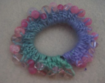 Crocheted soft purple and green hairband with various pink and clear beads