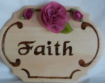 Faith wood burned plaque with small rosey-pink rosettes aside a single flower on the top,  on small pine marquee shape.
