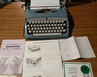 1965  light teal Brother DeLuxe portable manual typewriter with case, and original paperwork