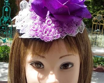 Fascinator hat.  Purple base with black trim.  Lace leaves with Swarovski crystals.  Purple roses, pearls, feathers and netting.