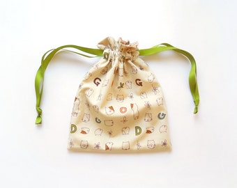 Small reversible drawstring bag, storage bag or gift bag with cute dogs and flowers; and small hearts, leaves and flowers on light brown