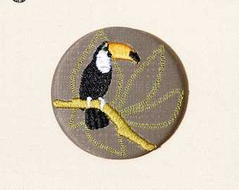Grande broche brodée oiseau toucan dans un arbre tropical