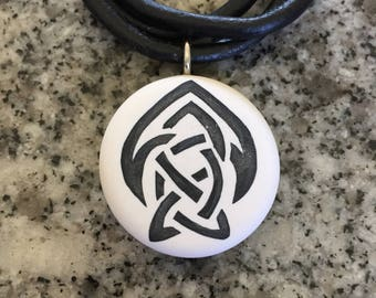 Celtic Brotherhood of the Arrow Symbol hand carved on a polymer clay white color background. Pendant comes with a FREE 3mm necklace