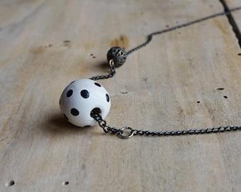 Asymmetrical pendant with ball of polka dots