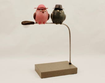 Whimsical bird sculptures, humorous bird sculpture, two chicks perched on light post, one mauve colored, one hunter green