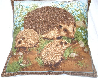 A Hedgehog and her two youngsters among pretty blue flowers in a garden cushion