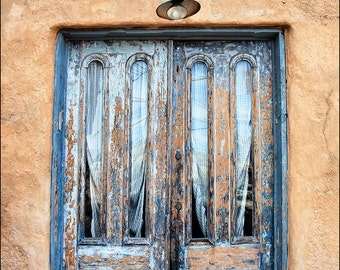 Wall art photograph of very colorful blue American Southwest weathered door on adobe wall with market ghost sign, peeling paint and cactus.