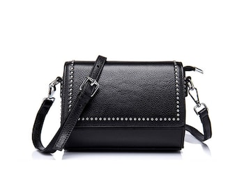 Small black leather crossbody bag with front flap closure and rivets