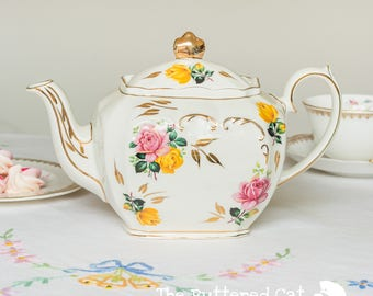 Beautiful vintage cube shaped teapot, pink and yellow roses on a cream base