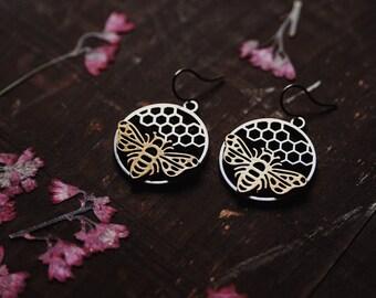 apiology. a pair of mixed metal geometric hexagon honeycomb and bee earrings