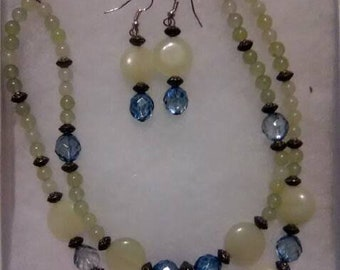 This is a hand made necklace and earring set made by me. It's a dual strand necklace made of young Jade and blue glass faceted beads.