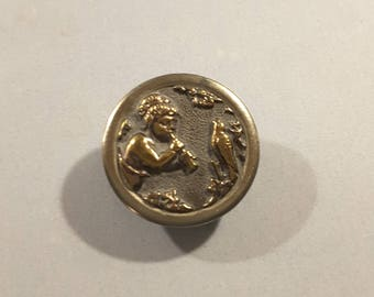 19th Century button of cherub playing a flute.