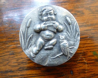 Silver button depicting baby playing pan pipes.