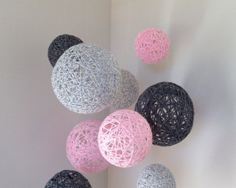 Mobile with marbled baby pink, marbled light grey, and dark grey yarn balls