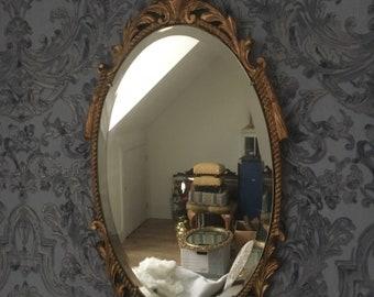 A small ornate gilt framed mirror by Atsonea