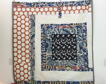 tapestry collage wall hanging-55 x 55. vintage fabrics on fabric. Reds,blues,blacks and white. light weight-hanging clips provided. Original