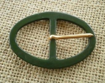 Oval belt buckle made of plastic, dark green color, size 7.5 / 5.3 cm