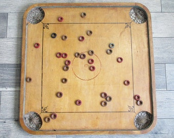 Antique Carrom Board with Mounted Game Pieces Ready for Display
