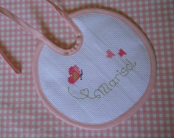 Custom bib with cross-stitch name embroidery entirely handmade.