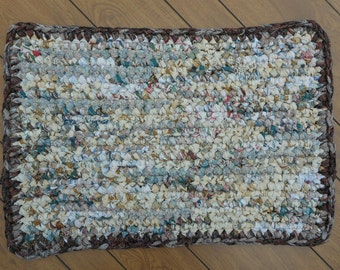 Rectangular neutral colored crocheted rag rug framed in a brown print (2017630-3)
